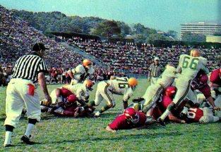 Arkansas in action during the 1964 season. At that time, Razorback Stadium's construction allowed fans a spectacular view of the Ozarks. Meanwhile, residents of Reid Hall could watch games from their dorm room.